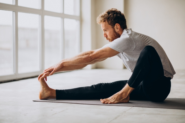Man practicing yoga on the mat at home